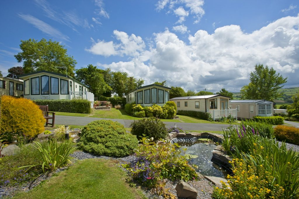 Tan Rallt Holiday Park pond and caravans with blue sky
